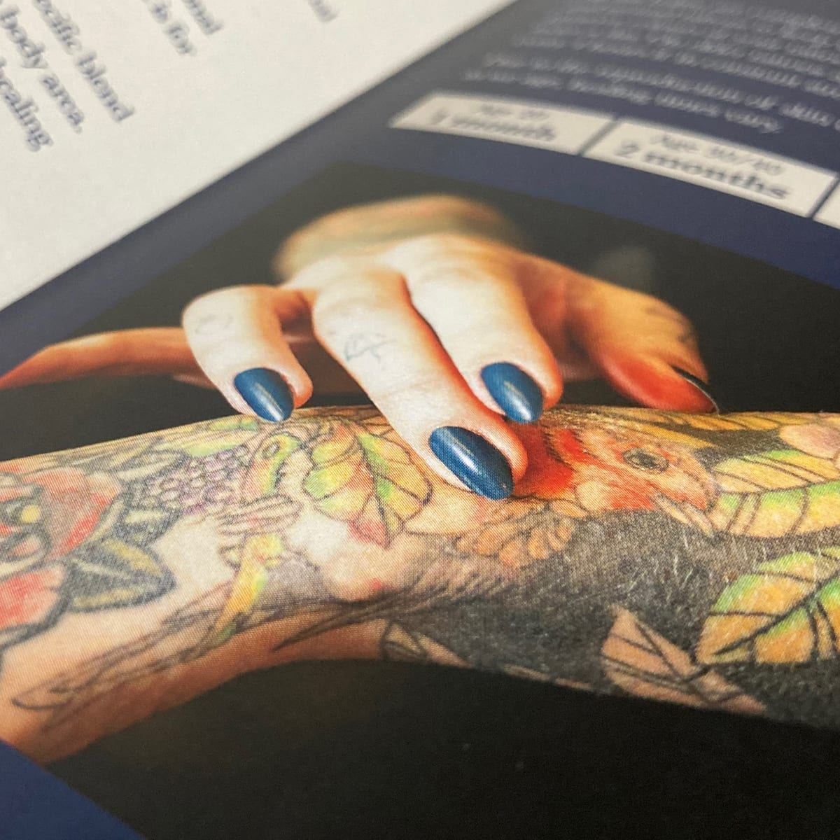A square crop of a page from a brochure showing a hand massaging balm onto a tattooed arm