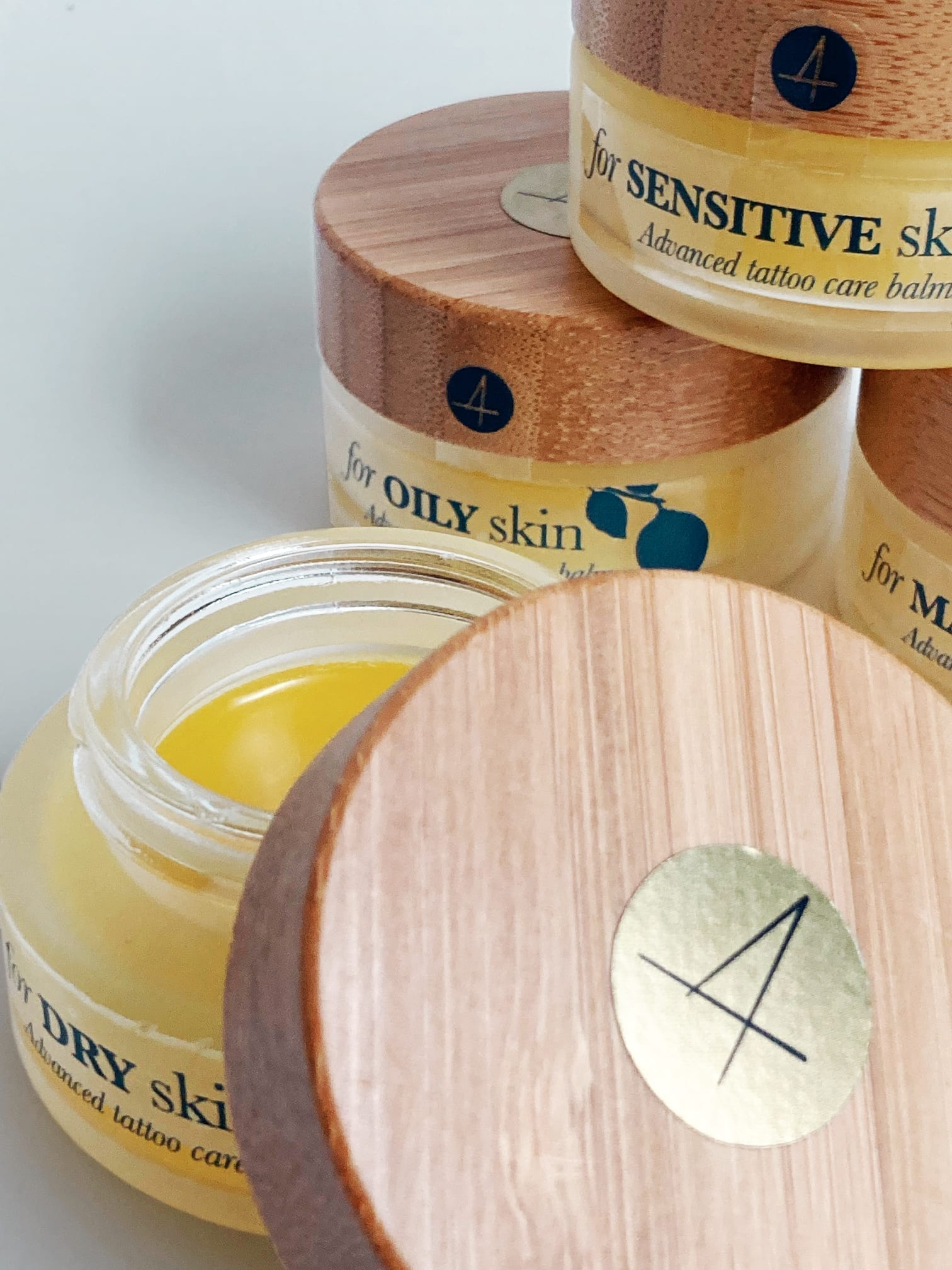 A stack of the all natural bamboo and glass packaging designed by Puur for Four Tattoo Care's range of balms.